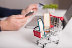 附近银行卡膝上型计算机和微型购物车在白色背景顶视图 免版税库存图片
