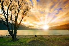 登陆太阳上升的天空scape在自然湖和雪mounta后的 免版税库存图片
