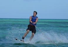 登陆跃迁的Wakeboarder在做一180以后在阿鲁巴 免版税图库摄影