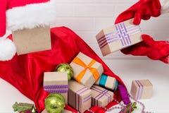 陌生人在礼物的一个红色袋子投入礼物 免版税图库摄影