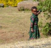陌生人微笑非洲儿童女孩在他的手上的拿着一根棍子。 免版税库存图片