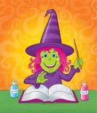 降一个魔法咒语的逗人喜爱的女孩巫婆 免版税库存图片