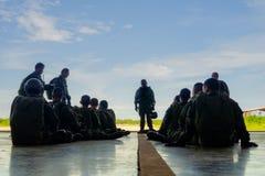 降伞团队负责人在飞机飞机棚向他充分的齿轮被装备的队伍介绍 免版税库存照片