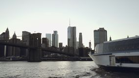 降低与一条游艇的曼哈顿地平线在从在East河的小船摄制的前景在布鲁克林大桥下 股票视频