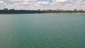 降低在海和浮体有绿色城市的背景的 影视素材