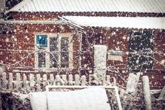 降雪冬天天气在有雪花和老房子窗口的村庄 免版税库存照片