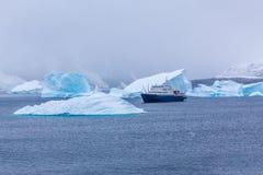 降雪和巡航划线员在蓝色冰山中在口岸Charcot, B 免版税库存图片