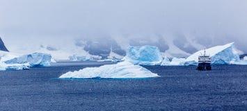 降雪和游轮在蓝色冰山中在口岸Charcot, Bo 免版税库存照片