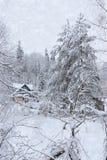 降雪在俄罗斯,一个小屋在森林 免版税库存照片