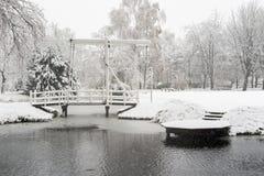 降雪在有桥梁和池塘的一个公园 库存图片