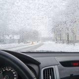 降雪在从汽车里边的城市 免版税库存照片