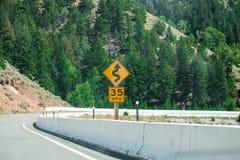 限速交通标志、35英里/小时和弯曲道路 库存照片
