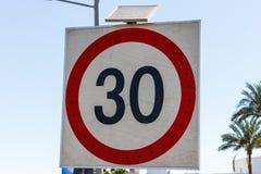 限速标志到30与在路的太阳电池板 免版税库存图片
