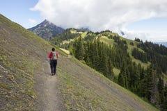 陡峭的山土坎足迹的女性远足者 免版税图库摄影