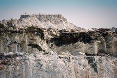 陡峭的岩石峭壁在一个露天开采矿大理石矿 免版税库存照片