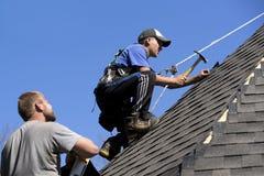 陡峭的沥青的盖屋顶的人 免版税库存照片