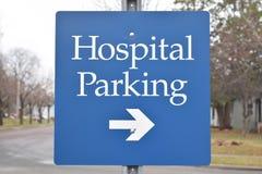 医院与箭头蓝色的停车处标志在颜色 免版税库存图片