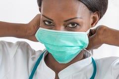 医院工作站的微笑的非裔美国人的护士在白色背景 免版税库存图片