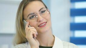 医院招待会的女性护士谈话在电话 免版税库存图片