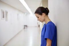 医院走廊的哀伤的女性护士 免版税库存照片