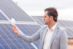 院长在他的手上拿着一个电灯泡以太阳电池板为背景 免版税库存图片