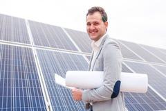 院长拿着一个笔记本,并且项目被折叠在他的胳膊下以太阳电池板为背景 库存照片