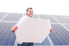 院长用在太阳电池板背景的项目手  底视图有一个角度 图库摄影