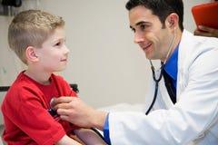 医院:Listens To Boy的Heart医生在检查屋子里 免版税库存图片