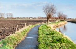 除一条蜿蜒地流的河以外的缩小的自行车路径。 库存图片