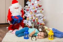除夕礼物的圣诞老人计划并且看睡着的在圣诞树两孩子前面 免版税库存图片