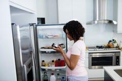 去除瓶的妇女从冰箱在厨房里 免版税库存照片