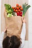 去除菜的妇女从购物袋 图库摄影