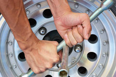 去除轮子坚果的强的手尝试  免版税库存图片