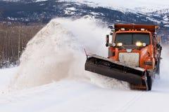除雪机在冬天风暴飞雪的清洁路 免版税图库摄影