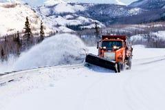 除雪机在冬天风暴飞雪的结算路 免版税图库摄影