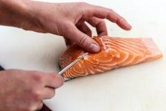 去除鱼骨的厨师从三文鱼 图库摄影