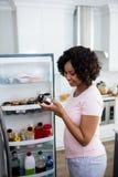 去除玻璃瓶子的妇女从冰箱 库存照片