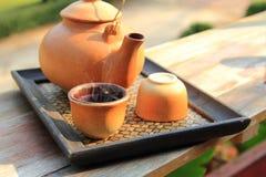 陶器茶壶的关闭有倒的在一个棕色杯子的热的茶在健康喝的桌安置在上午 免版税图库摄影