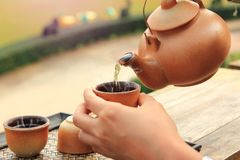 陶器茶壶的关闭有倒的在一个棕色杯子的热的茶在健康喝的桌被安置 库存图片