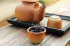 陶器茶壶的关闭有倒的在一个棕色杯子的热的茶在健康喝的桌被安置 免版税库存照片