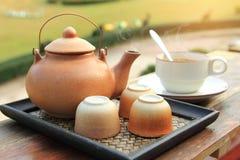 陶器茶壶的关闭有倒的在一个棕色杯子的热的茶在桌被安置 免版税库存照片