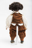 陶瓷一个深色的男孩的瓷手工制造玩偶棕色服装的 免版税库存照片