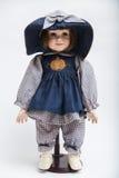 陶瓷在大帽子和蓝色礼服的瓷手工制造深色的玩偶 免版税库存照片