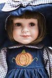 陶瓷在大帽子和蓝色礼服的瓷手工制造深色的玩偶 库存图片
