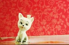 陶瓷在红色背景的小雕象逗人喜爱的白色猫 免版税库存照片