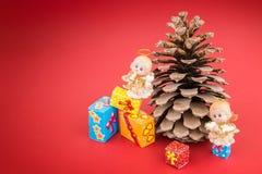 陶瓷天使、pincone和五颜六色的圣诞节礼物盒 免版税库存照片