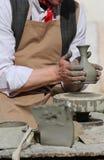 陶瓷工与车床一起使用在黏土花瓶的制造期间 免版税图库摄影