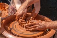陶瓷工在一个转动的瓦器轮子的泥罐教雕刻 库存图片