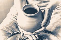 陶瓷工对负粗暴对白色黏土水罐生火  老牌葡萄酒 免版税库存图片