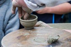 陶瓷工的手做在街道上的一个泥罐在市场 库存图片